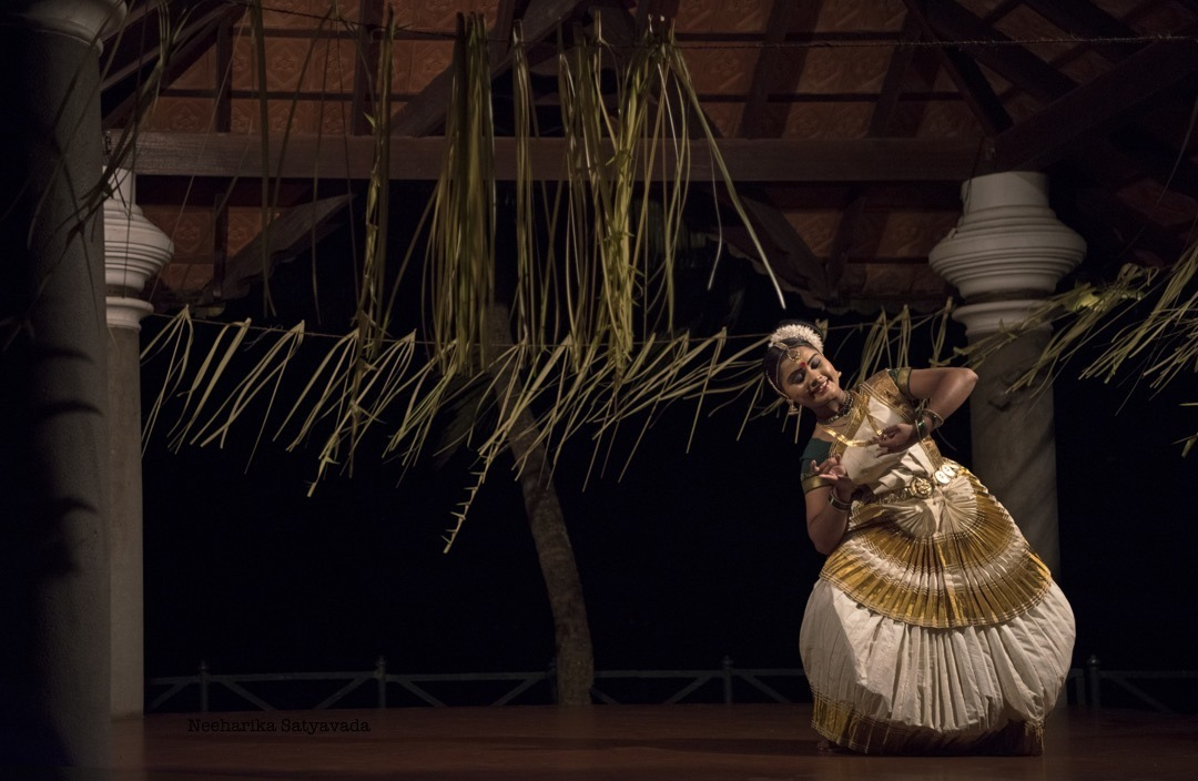 A dancer strikes a pose during her recital of Mohinyattam, with a backdrop of fluttering coconut fronds against the night sky.